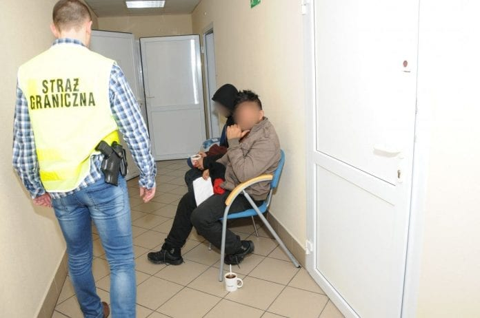 Funkcjonariusz Straży Granicznej pilnuje dwóch nielegalnych imigrantów