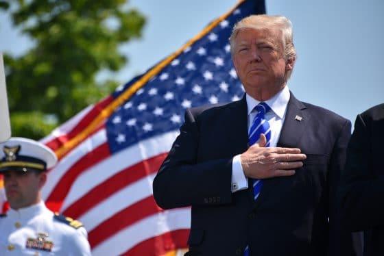 Donald Trump z ręką na sercu, na tle flagi Stanów Zjednoczonych