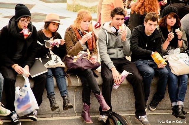 Grupa nastolatków - siedzą na murku i jedzą
